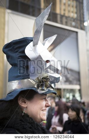 NEW YORK - MAR 27 2016: A woman wearing a silver rabbit head Easter bonnet walks along 5th Avenue on Easter Sunday for the traditional Easter Bonnet Parade in Manhattan on March 27, 2016.