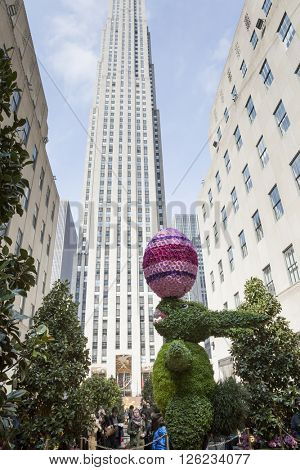 NEW YORK - MAR 27 2016: A giant revolving Easter Bunny topiary displayed at Rockefeller Center Channel Gardens Easter Sunday during the traditional Easter Bonnet Parade in Manhattan on March 27, 2016.