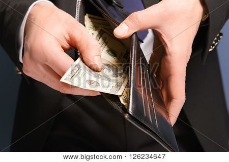 Man getting dollar banknotes out of purse