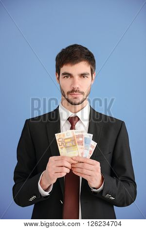 Attractive man in a suit holding fan of euro banknotes on blue background