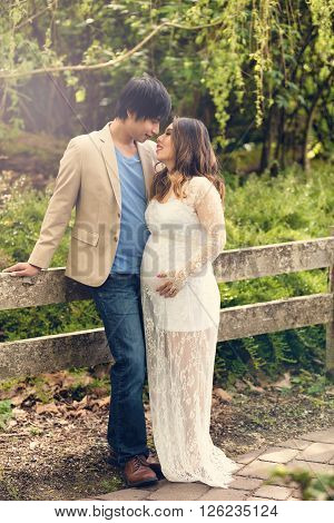 Expecting mom and dad leaning against split rail fence in the woods. Haze light effect applied to image.