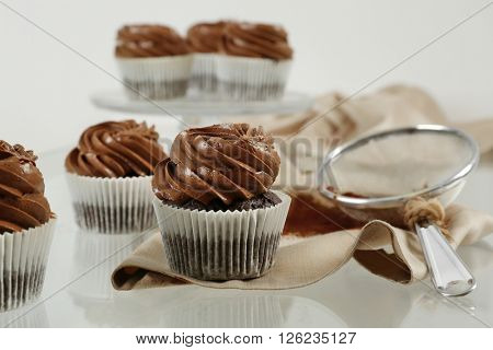 Chocolate cupcakes with sieve on light glass background, close up