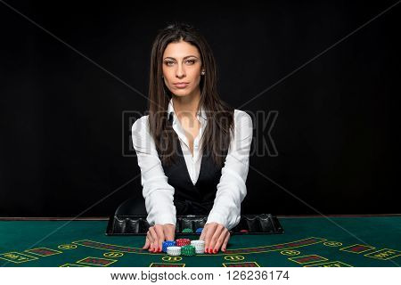 The beautiful girl, dealer, behind a table for game in poker, move chips