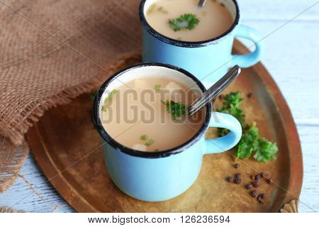 Mugs of soup on metal tray on a table