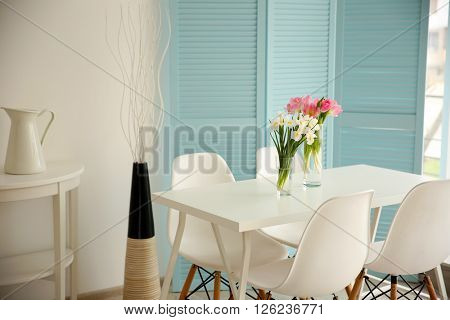 Beautiful tulips and irises on dinning table , indoors