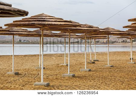 Straw sunshades on white rusty pillars at Dead Sea beach sand