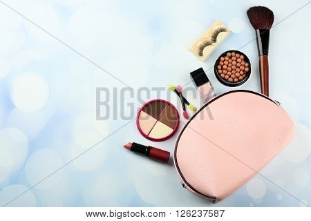 Makeup set with beautician, brush, false eyelashes and cosmetics on blue blurred background