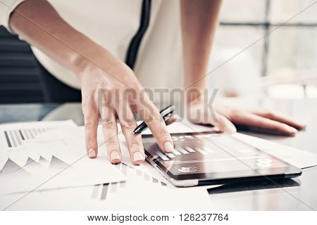 Photo woman reading market reports modern tablet and touching screen with worldwide stock exchange icons. Working process office. Horizontal.