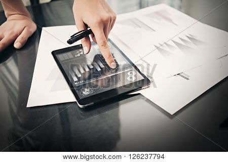 Photo woman working market reports modern tablet and touching screen with worldwide stock exchange icons. Documents for sign on the table. Horizontal.