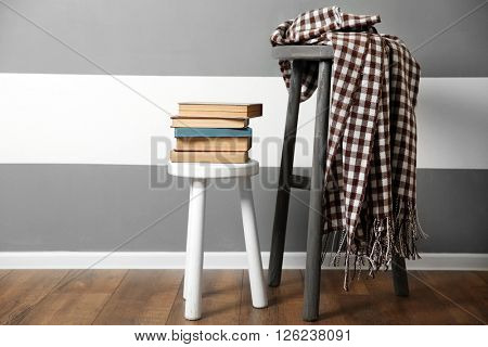 Stack of books on wooden stool and warm plaid against striped wall background