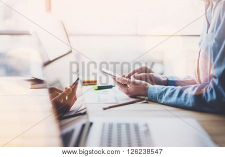 Working process photo. Account manager working wood table with new business project. Typing contemporary smartphone screen. Modern notebook reflections screen.Horizontal.
