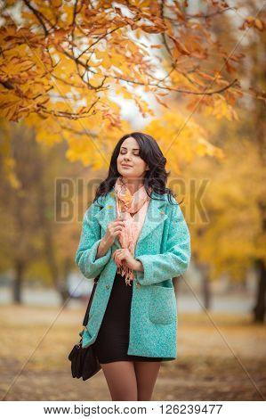 Beautiful young girl in fashionable coat in autumn garden