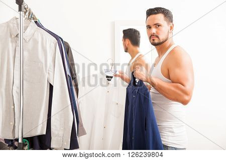 Young Man Getting Dressed In His Bedroom