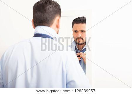 Man Tying A Necktie In Front Of Mirror