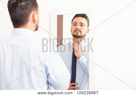 Hispanic Young Man Putting On A Necktie