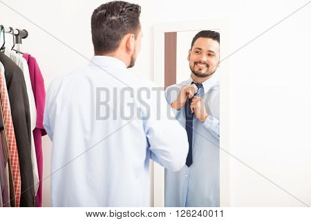 Man Putting On Necktie In A Dressing Room