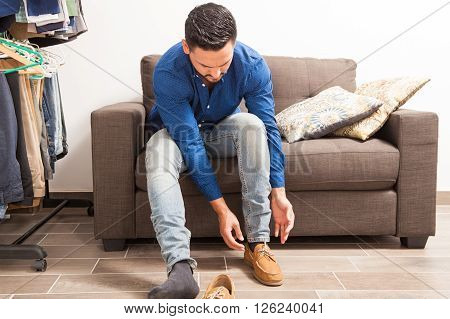 Young Man Putting Shoes On In Dressing Room
