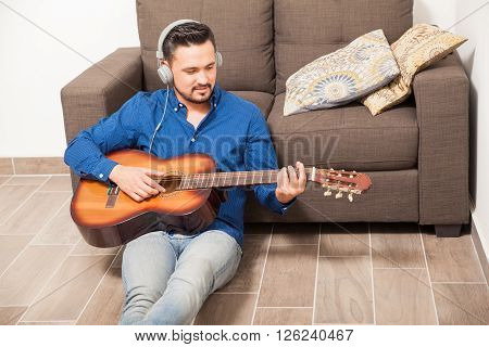 Guy With Headphones Playing The Guitar At Home