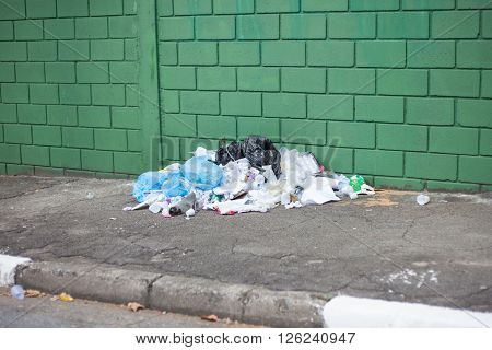 SAO PAULO, SP - BRAZIL: April 10th 2016 garbage pile on street in front of green wall in sidewalk on street near Avenida Paulista in Sao Paulo April 10, 2016.