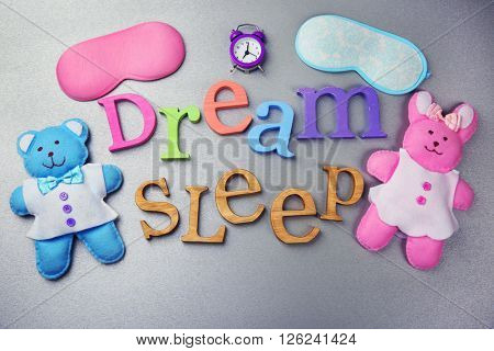 Words Dream and Sleep with  little toys  on a grey background