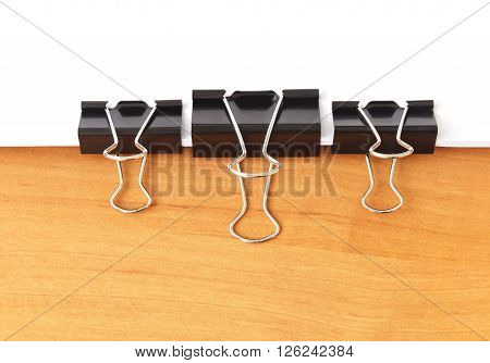 Three paperclips stapling papers on the table