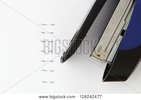Blue stapler and staples with paper on the table