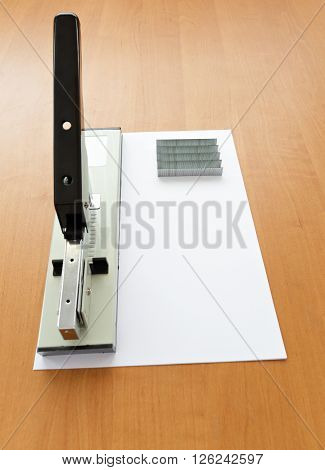Stapler and staples with paper on the table