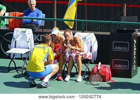 KYIV UKRAINE - APRIL 17 2016: Captain of Ukraine National Team Mikhail Filima (L) and players Kateryna Bondarenko and Olga Savchuk during BNP Paribas FedCup pair game Ukraine vs Argentina