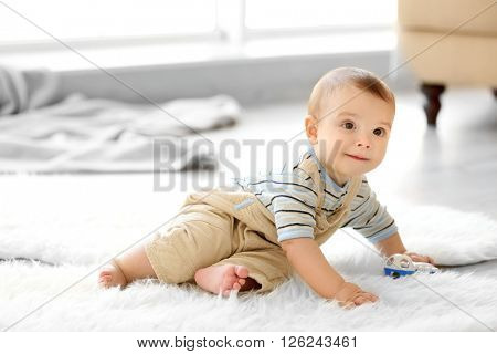 Little baby boy with a toy sitting on the floor at home