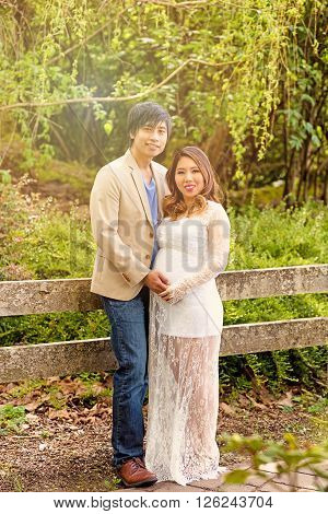 Expecting mom and dad leaning against split rail fence while looking forward with woods in background. Haze light effect applied to image.