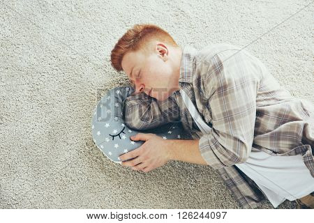 Young tired man sleeping on the floor