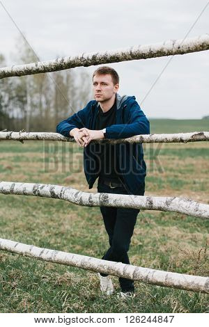 Young frowning man standing in a field leaning against the fence of birch. Rest from the city bustle