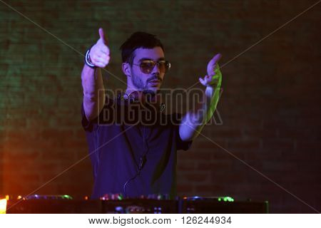 DJ playing music at mixer on blurred brick wall background