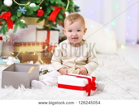 Funny baby girl with gift boxes and Christmas tree on background