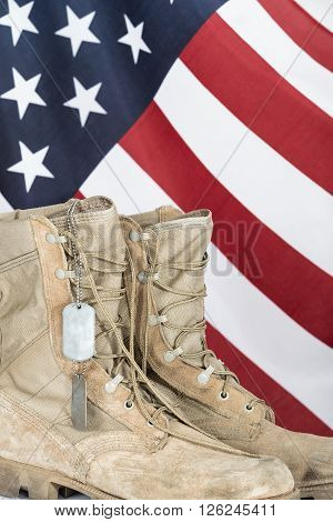 Old combat boots and dog tags with American flag in the background