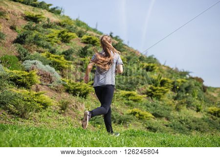 Photo of happy long-haired young blonde woman doing running activities. Back view.** Note: Soft Focus at 100%, best at smaller sizes
