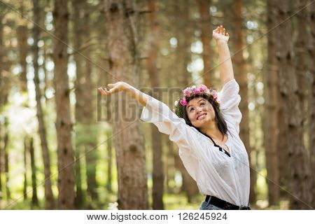 Cheerful boho young woman in white sheer bohemian fashion blouse, with pink floral crown, in park in summer, standing with hands raised, smiling, looking up. Medium retouch, natural light.