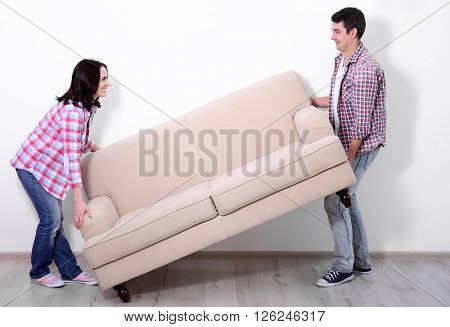 Young couple carrying sofa in their new house.