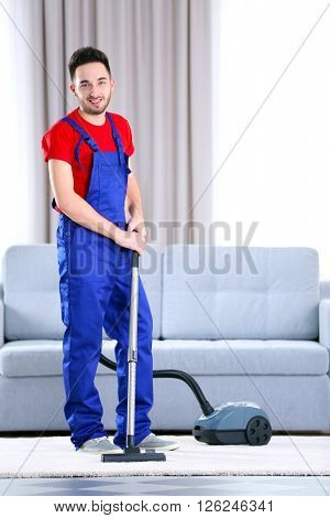 Man cleaning in the flat with vacuum cleaner