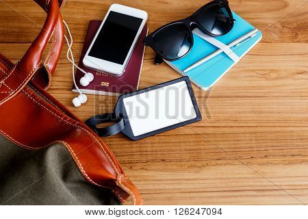 Travel Bag And Blank Tag On Wood Table