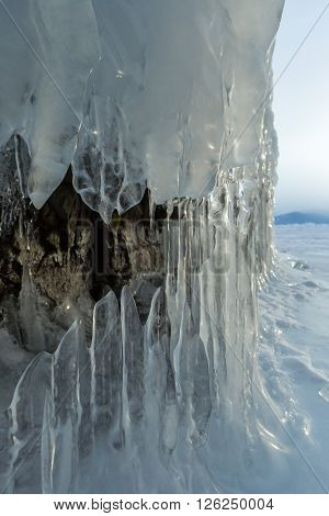 Ice stalactites and stalagmites in the rock. Beautiful winter landscape in the Lake Baikal.