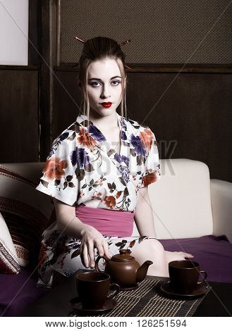 beautiful girl dressed as a geisha and preparing tea ceremony. Geisha makeup and hair dressed in a kimono. The concept of traditional Japanese values.