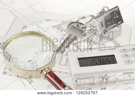 key with keychain in the form of a silver-colored house on a background of architectural drawing, electronic calculator &  magnifying glass