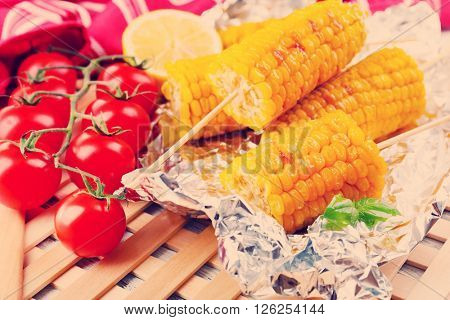 Grilled corn cobs and fresh tomatoes on wooden table