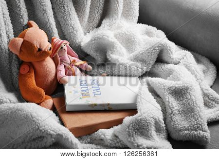 Rag toys with fairy tales books on bedspread. Childhood concept