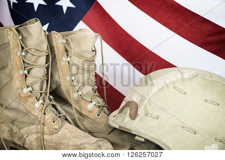 Old combat boots and helmet with American flag in the background