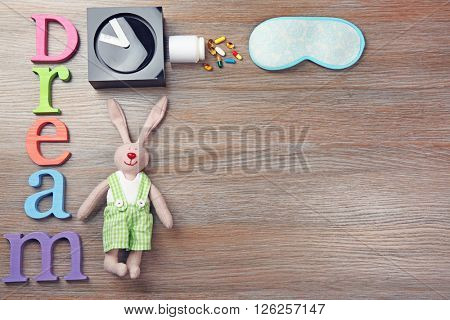 Word Dream with little toy, clock and mask on a wooden background