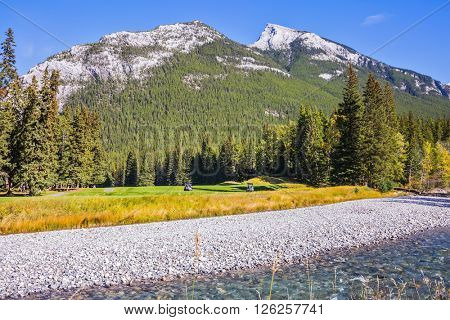 Beneaped autumn stream with a pebbly bottom flows among the mountains. Magnificent picturesque valley in Banff National Park