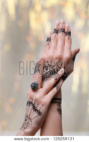 Female hands with henna tattoo on bright blurred background