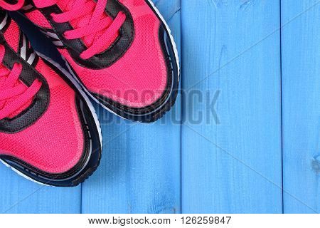 Pair of pink sport shoes on blue boards concept of healthy and active lifestyles copy space for text or inscription